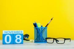 11月8日 天8月,在黄色背景的木颜色日历与办公用品 秋天时间 免版税库存图片