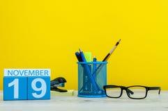 11月19日 天19月,在黄色背景的木颜色日历与办公用品 秋天时间 图库摄影