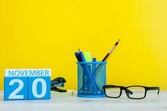 11月20日 天20月,在黄色背景的木颜色日历与办公用品 秋天时间 免版税库存照片