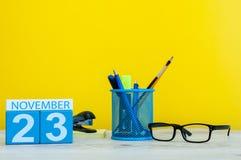 11月23日 天23月,在黄色背景的木颜色日历与办公用品 秋天时间 库存图片