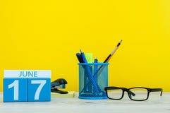 6月17日 天17月,在黄色背景的日历与办公室suplies 夏时在工作 库存照片