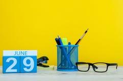 6月29日 天29月,在黄色背景的日历与办公室suplies 夏时在工作 免版税库存照片