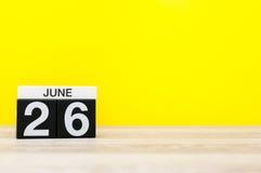 6月26日 天26月,在黄色背景的日历 调遣结构树 文本的空的空间 国际天反对 免版税库存照片