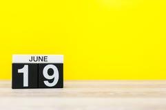 6月19日 天19月,在黄色背景的日历 调遣结构树 文本的空的空间 库存照片