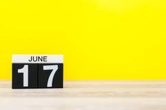 6月17日 天17月,在黄色背景的日历 调遣结构树 文本的空的空间 免版税图库摄影
