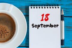 9月18日 天18月,早晨有活页日历的热奶咖啡杯子在分析家工作场所背景 秋天 库存照片