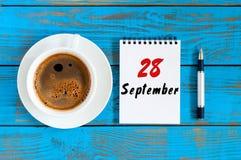 9月28日 天28月,早晨有活页日历的咖啡杯在财政顾问工作场所背景 免版税图库摄影