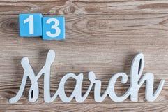 3月13日 天13行军月,在木桌背景的日历与被雕刻的文本 春天…上升了叶子,自然本底 免版税图库摄影