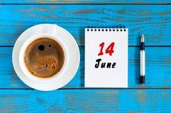 6月14日 日历的6月14日,在蓝色背景的图象与早晨咖啡杯 夏日,顶视图 免版税库存图片