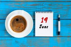 6月19日 日历的6月19日,在蓝色背景的图象与早晨咖啡杯 夏日,顶视图 库存照片