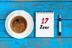 6月17日 日历的6月17日,在蓝色背景的图象与早晨咖啡杯 夏日,顶视图 免版税库存照片
