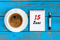 6月15日 日历的6月15日,在蓝色背景的图象与早晨咖啡杯 夏日,顶视图 免版税库存照片