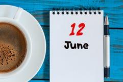 6月12日 日历的6月12日,在蓝色背景的图象与早晨咖啡杯 夏日,顶视图 库存照片