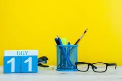 7月11日 日历的7月11日,在黄色背景的图象与办公用品 新的成人 文本的空的空间 库存图片