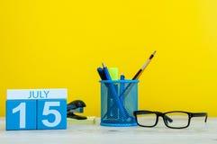 7月15日 日历的7月15日,在黄色背景的图象与办公用品 新的成人 文本的空的空间 免版税库存图片