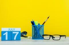 7月17日 日历的7月17日,在黄色背景的图象与办公用品 新的成人 文本的空的空间 免版税库存照片
