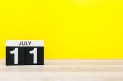 7月11日 日历的7月11日,在黄色背景的图象 新的成人 文本的空的空间 库存照片