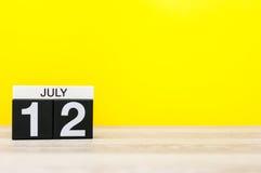 7月12日 日历的7月12日,在黄色背景的图象 新的成人 文本的空的空间 库存照片