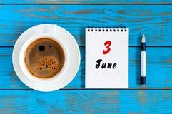 6月3日 日3,每天日历和早晨咖啡杯在蓝色木背景 夏天概念,上面 库存图片