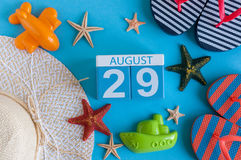 8月29日 8月29日日历的图象与夏天海滩辅助部件和旅客成套装备的在背景 调遣结构树 免版税库存图片