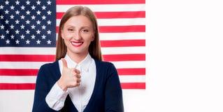 7月4日 美国旗子背景的微笑的少妇 免版税库存图片