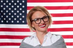 7月4日 美国旗子背景的微笑的少妇 免版税库存照片