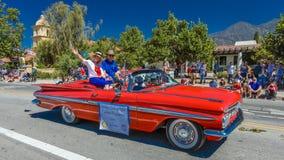 2016年7月4日- Ojai加利福尼亚的公民庆祝美国独立日- 1959红色有挥动的Impalla薛佛列敞篷车 库存照片