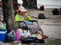2016年12月31日otres使西哈努克柬埔寨,海滩的年轻亚裔妇女靠岸使用她的智能手机社论 免版税库存照片