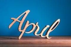 4月-第2个月春天 在深蓝背景的木被雕刻的词 拟订在傻瓜天,复活节4月1日, 免版税库存照片