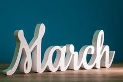 3月-第1个月春天 在深蓝背景的木被雕刻的词 拟订在母亲节,复活节3月8日, 免版税图库摄影