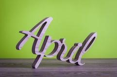4月-被雕刻的文本木在浅绿色的背景 第二个春天月 免版税库存图片