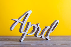 4月-被雕刻的文本木在淡黄色背景 第二个春天月 图库摄影