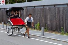 2012年6月- Arashiyama,日本:拉扯有两个人坐的挥动的一个亚裔人一辆被拉扯的人力车在照相机 免版税库存照片