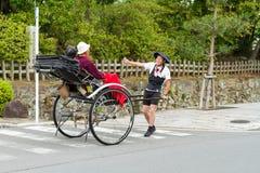 2012年6月- Arashiyama,日本:拉扯有两个人的一个亚裔人一辆被拉扯的人力车安装和移动远离照相机 免版税库存图片