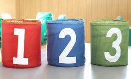 有一两个和三个数字的五颜六色的罐头在学校 图库摄影