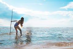 有一个三叉戟的女孩在他的手上看海表面 库存图片