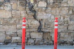有一个主要裂缝的老墙壁,与警告岗位 图库摄影