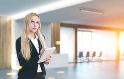有一个习字簿的白肤金发的妇女在办公室 免版税图库摄影
