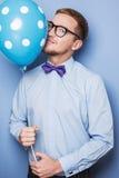 有一个五颜六色的气球的年轻人在他的手上 党,生日,华伦泰 免版税库存图片