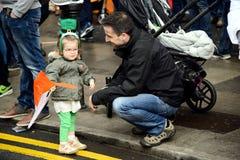 有一个人的一个小逗人喜爱的女孩在圣帕特里克` s天ParadeÂ在都伯林,爱尔兰, 2015年3月18日 免版税图库摄影