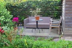 有一个休息室沙发的庭院露台在花之间 图库摄影