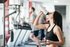 有一个体育机构的美丽的性感的妇女在黑白运动服在健身房训练 免版税库存照片