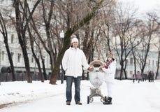有一个儿子和婴孩的年轻人走在多雪的公园的婴儿推车的 库存照片
