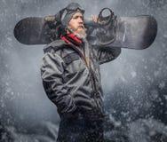 有一个充分的胡子的残酷红头发人挡雪板在冬天帽子和防护玻璃在雪板运动外套穿戴了 库存照片