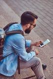 有一个充分的胡子的游人和理发,有背包的佩带的便衣,发短信在智能手机,坐a 图库摄影