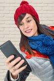 有一个冬天盖帽的少妇,使用智能手机 库存照片