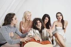 有一个凉快的姿态的年轻男性吉他弹奏者在女性小组中 库存图片