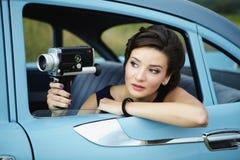 有一个减速火箭的电影摄影机的美丽的夫人 库存照片