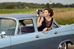 有一个减速火箭的电影摄影机的美丽的夫人 免版税库存照片