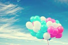 有一个减速火箭的instagram过滤器生日快乐的作用、概念在夏天和婚礼蜜月的五颜六色的气球 免版税库存图片